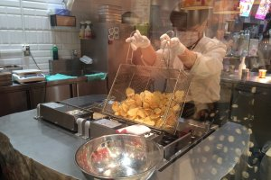 Peeking through the glass window, attentively watching them prepare freshly fried potato chips. Get them while they're hot!