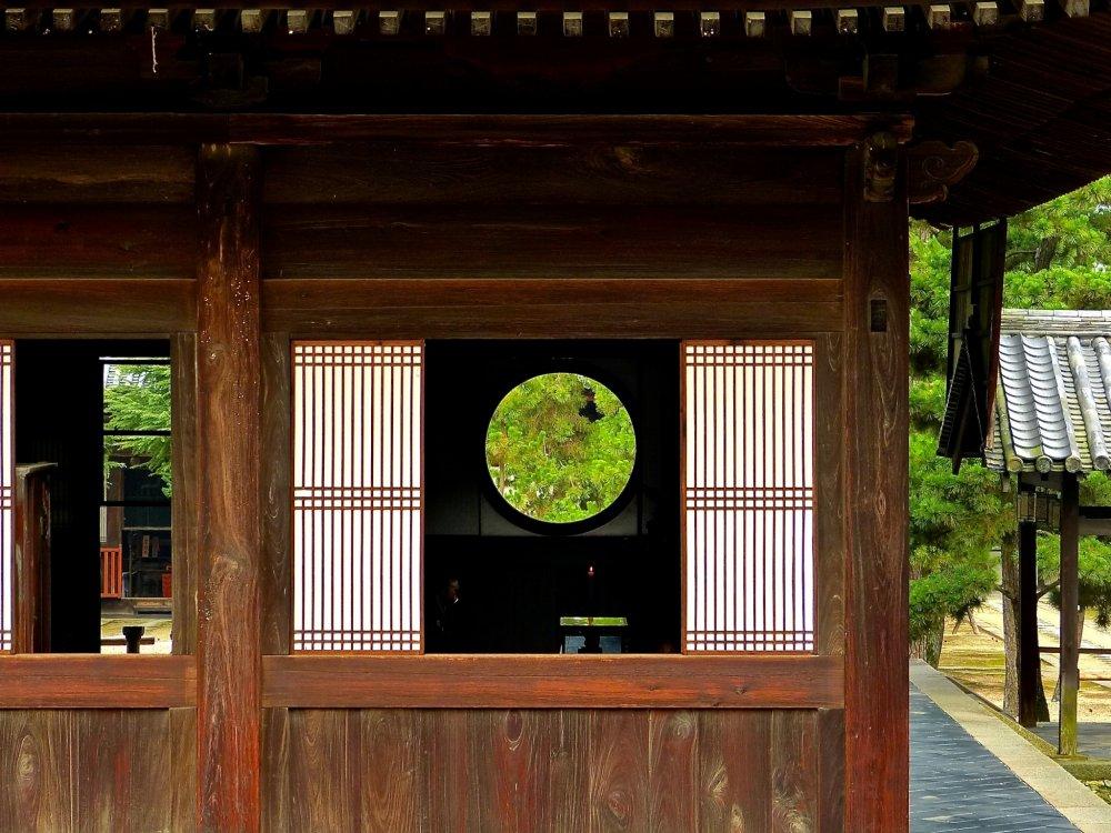 De la verdure derrière une fenêtre ronde