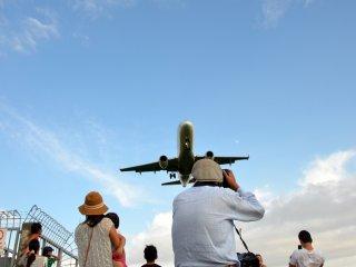 착륙하는 비행기 사진을 찍는 현지인