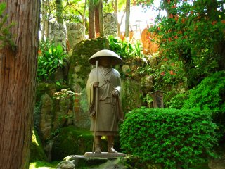 Statue of Monk Shinran standing silently in the woods at the back of the Main Hall