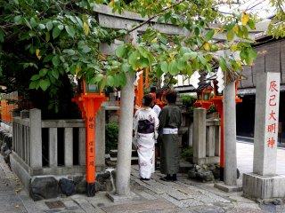 A couple wearing kimono pray at Tatsumi Daimyojin Shrine
