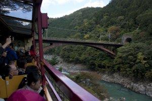 มุมนี้รถไฟสายโรแมนติก Sagano Romantic Train จะผ่านสะพานข้ามแม่น้ำโฮะซึ (Hozugawa River) ซึ่งเป็นสะพานของรถไฟJR Sanin Main Line ที่ให้บริการอยู่ในเส้นทางปัจจุบัน