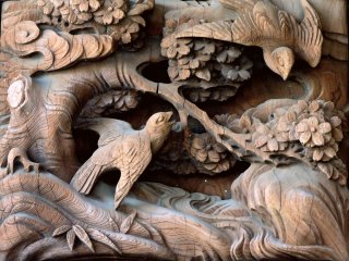 Several carved wooden scenes feature birds