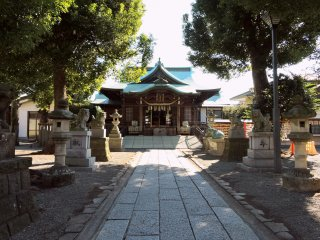 Stone lanterns and two ox statues stand beside the straight path to the shrine