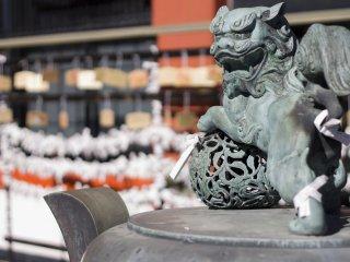 Перед залом Narita Mountain Fudou находится декоративная курильница с орнаментами и место, где можно повесить своё желание для Богов