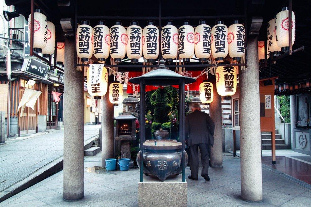 On n'offre pas d'argent ici, on arrose la statue de Fudô