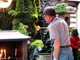 Un homme est en train de prier et d'arroser la statue
