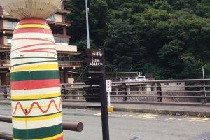 An aging kokeshi guards the bridge crossing the river