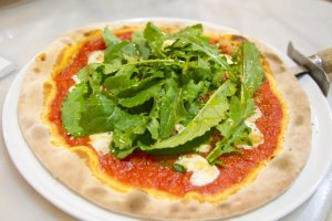 Pizza margarita with fresh rucola (arugula)