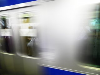 A JR Joban Line train departing from Kita Senju station in Tokyo. It was only later that realised there was a reflection in the window of a person holding a bag.