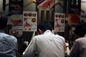 Diners slurping up their noodles at Kanisenmon Keisuke.