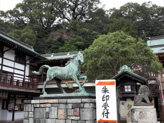 Seibo Kitamura, famous for Nagasaki's Peace Park Statue, created this vibrant horse statue in commemoration of the 60th anniversary of Emperor Hirohito's accession in 1985. Note the completely non-related signage directing visitors to the desk selling shrine seal stamps, a popular shrine souvenir.