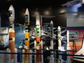 Various rocket designs line the wall.