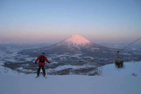 A skier decending with Mt. Yotei in the background