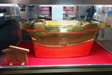 <p>A golden tub sits at the entrance. I am not sure of its origin or why it is in the Hula Museum.&nbsp;</p>