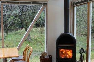 カフェ客室には薪ストーブが赤く燃えていた。全面ガラス張りでとても見晴らしがよい