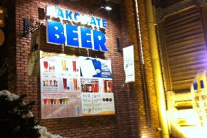 ด้านหน้าของร้าน Hakodate Beer Hall ยามค่ำคืนที่หิมะโปรยปราย