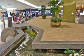 在機場商城,你可以在流水泉旁休息。許個願並丟個銅板會為你帶來好運喔!
