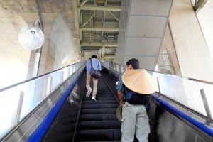 Naiki eskalator untuk ke Terminal Bus Maiko, yang terletak di kaki Jembatan Besar Selat Akashi. Itu langsung terhubung ke Stasiun JR Maiko. Pria yang lehernya menggantung topi bambu pasti adalah seorang peziarah yang menuju Tokushima di Shikoku