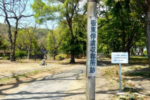 Wooden board says, 'Bando POW Camp Site'
