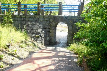 <p>This stone bridge was reconstructed to resemble the original bridge German POW made. The original bridge is still preserved in the Oasahiko Shrine grounds in the area. When they were living in the camp, they visited the shrine, and to commemorate the visit constructed and donated the so-called, &#39;Spectacles Bridge&#39; to the shrine.</p>