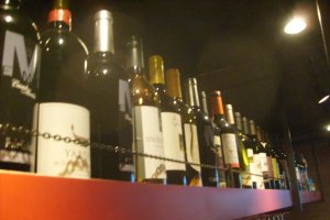 Wine stored on a shelf over the bar, safely out of the comedians' reach