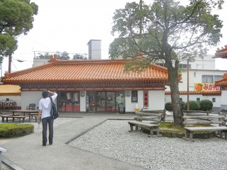 """Inside of the park, facing the small gift shop where visitors can purchase """"Jofuku tea"""" and """"Jofuku wine."""""""