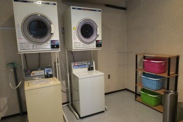 <p>Laundry room with coin-operated washing machines and drying machines, though a laundry service is also available.</p>