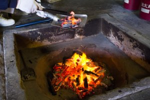 ถ่านไฟถูกเก็บมารวมกันใช้อุ่นแผ่นไม้สำหรับตากใบชา