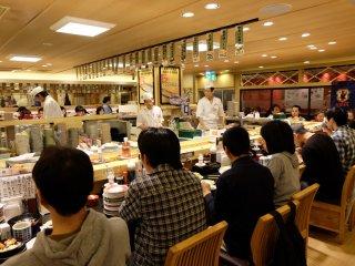 ภายในร้านเป็นเคาว์เตอร์มีคนปั่นซุชิยืนตรงกลาง หากใครมาเป็นกลุ่มก็มีโต๊ะนั่งให้บริการเช่นกัน