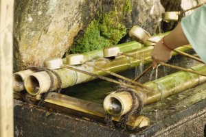 L'eau avec laquelle les visiteurs se lavent avant de pénétrer dans le sanctuaire. Le processus est très codifié; après avoir récupéré de l'eau «tombante» dans une cuillère, il faut s'humecter la main gauche, puis la droite, puis récupérer de l'eau au creux de sa paume qu'on porte ensuite à sa bouche avant de la recracher dans le fossé.