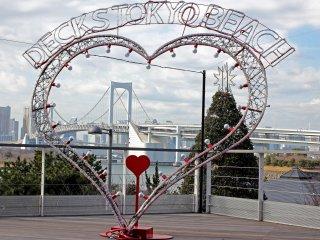 """Depuis le """"Decks Tokyo Beach"""" de la zone commerciale : à travers ce dispositif digne de la Saint-Valentin, on tombe naturellement amoureux du Rainbow Bridge!"""