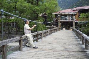 A visitor sketching the beauty of the Hokata mountain range at the Kappabashi bridge
