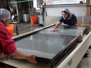 大型の木枠で紙を漉いている