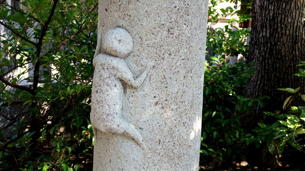 A child (?) clinging to the stone lantern