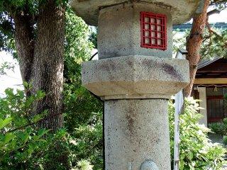 The child is hanging on to the stone pillar of the Koshin Lantern
