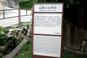 '야마자토구치 데마스구카타'라는 표지판은 돌담으로 둘러싸인 정사각형 공간이다