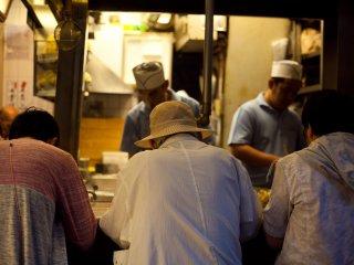 Гости уживанают в одном из множества магазинчиков якитори