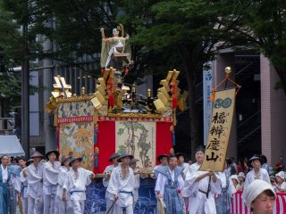 """Hashi-Benkei-Yama (橋弁慶山) During the Yamaboko Junko (山鉾巡行). This float derives its name from a Noh drama titled """"Hashi-benkei"""" and features a famous scene in which Benkei, a warrior monk in armor with a long-handled sword, is fighting with the young Ushiwaka-maru, who stands on the parapet of the Gojohashi bridge on the Kamo River"""