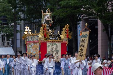 <p>Hashi-Benkei-Yama (橋弁慶山) During the Yamaboko Junko (山鉾巡行). This float derives its name from a Noh drama titled &ldquo;Hashi-benkei&rdquo; and features a famous scene in which Benkei, a warrior monk in armor with a long-handled sword, is fighting with the young Ushiwaka-maru, who stands on the parapet of the Gojohashi bridge on the Kamo River</p>