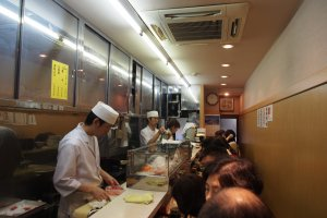 The inside one of the restaurants at the Tsukiji Fish Market – people are neatly packed in while the chefs efficiently prepare the meals