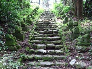 Những hình dạng đá của Rakan, học trò của Đức Phật, dọc theo các bậc đá để đến ngôi đền