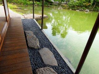 Di luar beranda, batu untuk injak di atas batu bulat dan kolam