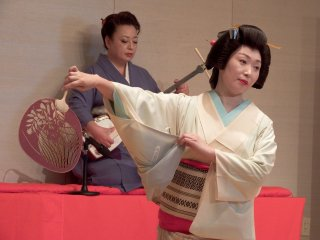 Ms. Shiori,summer fan in her hand, is posing in motion. Ms. Madoka is playing Shamisen in the background
