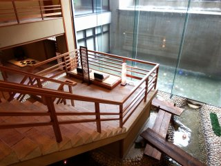 The stairs connecting the first floor lobby and the second floor. There are reclining sofas on the staircase landing