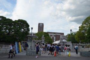 บรรยากาศประตูทางเข้า มีนักเรียนม.ปลายจำนวนมากมายืนรอถ่ายรูปคู่กับป้ายชื่อมหาวิทยาลัย
