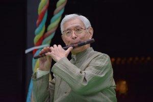 Ông Sukeyasu Shiba, một nghệ sĩ nổi tiếng của dòng nhạc Gagaku, chơi fue (sáo Shino) cho khán giả nghe một cách chăm chú