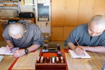 <p>Monks painting goshuinchou across from the large red temple (Konpon Daito) in Koyasan</p>