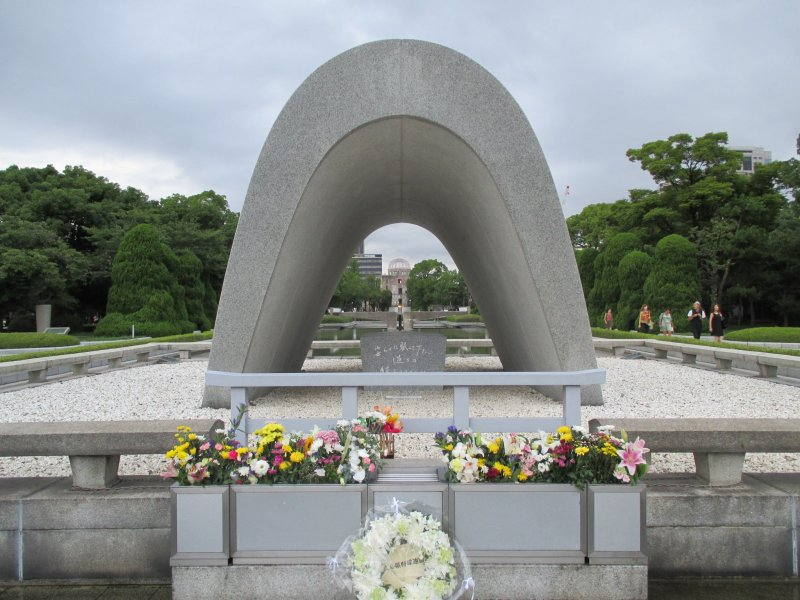 <p>The cenotaph for the A-bomb victims. A chest holds a registry of &nbsp;victims who have passed. The Peace Flame and the A-bomb Dome can be seen through it.</p>