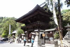 ประตูไม้ที่สวยงดงามหน้าศาลเจ้า ตรงประตูมี 'โคะไมนุ' (Komainu) สัตว์ครึ่งสุนัขครึ่งสิงโต อยู่ถึงสี่ตัวยืนอารักขาขับไล่ภูตและสิ่งช่วยร้ายกันอย่างแข็งขัน